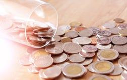 Το νόμισμα χρημάτων είναι διεσπαρμένο από ένα μπουκάλι γυαλιού Στοκ εικόνα με δικαίωμα ελεύθερης χρήσης