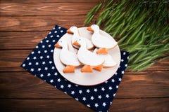 Το νόστιμο μελόψωμο απορροφά τα διαμορφωμένα μπισκότα σε ένα πιάτο με το αυτί του σίτου σε ένα ξύλινο υπόβαθρο Στοκ φωτογραφία με δικαίωμα ελεύθερης χρήσης