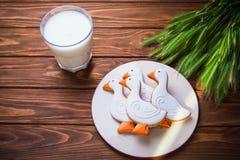 Το νόστιμο μελόψωμο απορροφά τα διαμορφωμένα μπισκότα σε ένα πιάτο με το ποτήρι του γάλακτος και με το αυτί του σίτου σε ένα ξύλι Στοκ Φωτογραφίες