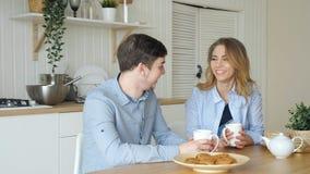 Το ξανθοί κορίτσι και ο τύπος έχουν το τσάι κατανάλωσης προγευμάτων στην κουζίνα φιλμ μικρού μήκους