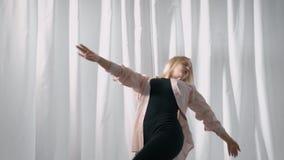 Το ξανθό έφηβη κάνει τις μετακινήσεις χορού με το χέρι και τα πόδια στο δωμάτιο με τις ελαφριές κουρτίνες στην ημέρα απόθεμα βίντεο