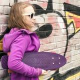 Το ξανθό έφηβη κρατά skateboard, αστικός τουβλότοιχος Στοκ Εικόνες