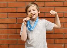 Το ξανθό αγόρι είναι ευτυχές χρυσό μετάλλιο - πρωτοπόρος Στοκ Εικόνα