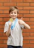 Το ξανθό αγόρι είναι ευτυχές χρυσό μετάλλιο - πρωτοπόρος Στοκ Εικόνες