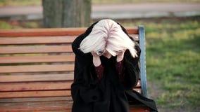 Το ξανθό εξωτερικό γυναικών πηγαίνει στο πλαίσιο κάθεται σε έναν πάγκο δοκιμάζει την πίεση λυπημένος ένας δυσαρεστημένος πονοκέφα φιλμ μικρού μήκους