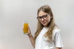 Το ξανθό ευτυχές κορίτσι κρατά στο χέρι της ένα ποτήρι του φρέσκου χυμού Υγιεινή διατροφή Χορτοφάγος και vegan στοκ φωτογραφίες