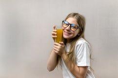 Το ξανθό ευτυχές κορίτσι κρατά στο χέρι της ένα ποτήρι του φρέσκου χυμού Υγιεινή διατροφή Χορτοφάγος και vegan στοκ φωτογραφία με δικαίωμα ελεύθερης χρήσης