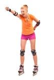 Το ξανθό κάνοντας πατινάζ κορίτσι κυλίνδρων τρυπά τον αέρα με διατρητική μηχανή. Στοκ Φωτογραφία