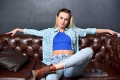 Το ξανθό κορίτσι κάθεται σε έναν καφετή καναπέ στο υπόβαθρο μιας GR Στοκ φωτογραφία με δικαίωμα ελεύθερης χρήσης