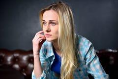 Το ξανθό κορίτσι κάθεται σε έναν καφετή καναπέ στο υπόβαθρο μιας GR Στοκ εικόνα με δικαίωμα ελεύθερης χρήσης
