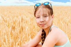 Το ξανθό κορίτσι κάθεται σε έναν τομέα με το σίτο Στοκ Φωτογραφίες