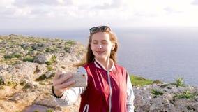 Το ξανθό κορίτσι κάνει selfie στο υπόβαθρο της καταπληκτικής φύσης, βράχοι, θάλασσα, πρασινάδα Μακρυμάλλη χαμόγελα κοριτσιών εφήβ απόθεμα βίντεο