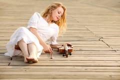 Το ξανθό κορίτσι με ένα βιολί υπαίθριο Στοκ Εικόνες