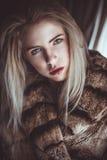 Το ξανθό κορίτσι με ένα κρύο κοιτάζει επίμονα στοκ φωτογραφία