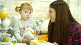 Το ξανθό κορίτσι μικρών παιδιών με τη μητέρα brunette ανοίγει τα κιβώτια δώρων Χριστουγέννων στο σπίτι απόθεμα βίντεο