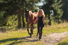 Το ξανθό κορίτσι οδηγεί το άλογο από τα ηνία Στοκ φωτογραφία με δικαίωμα ελεύθερης χρήσης