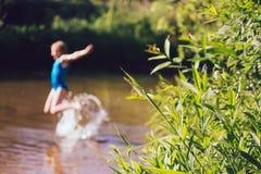 Το ξανθό κορίτσι παιδιών έχει τη διασκέδαση στον ποταμό Στοκ Φωτογραφίες