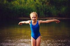 Το ξανθό κορίτσι παιδιών έχει τη διασκέδαση στον ποταμό Στοκ φωτογραφία με δικαίωμα ελεύθερης χρήσης