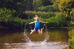 Το ξανθό κορίτσι παιδιών έχει τη διασκέδαση στον ποταμό Στοκ φωτογραφίες με δικαίωμα ελεύθερης χρήσης