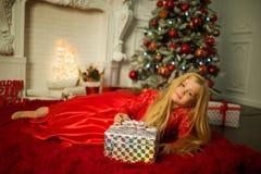 Το ξανθό κορίτσι πορτρέτου αρκετά φορά διακοσμημένη φορεμάτων μόδας το κόκκινο πλησίον χριστουγεννιάτικο δέντρο Στοκ Εικόνες