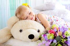 το ξανθό κορίτσι που αγκαλιάζει μεγάλο άσπρο teddy αντέχει στοκ φωτογραφία με δικαίωμα ελεύθερης χρήσης