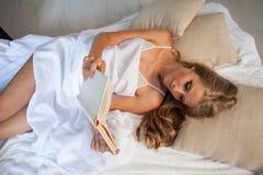 Το ξανθό κορίτσι που διαβάζει ένα βιβλίο βρίσκεται στο κρεβάτι στοκ φωτογραφία