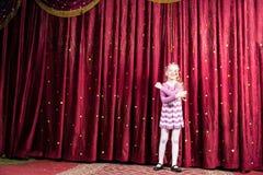 Το ξανθό κορίτσι που φορά τον κλόουν αποτελεί τη στάση στη σκηνή στοκ εικόνα