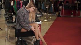 Το ξανθό κορίτσι προσπαθεί στα παπούτσια σε ένα κατάστημα, κάθεται στον πάγκο και κοιτάζει με τα πόδια απόθεμα βίντεο