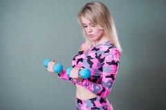 Το ξανθό κορίτσι ρόδινο sportswear κάλυψης συμμετέχει στους αλτήρες Δικέφαλοι μυ'ες workout Μέση επάνω στο πορτρέτο στοκ εικόνες