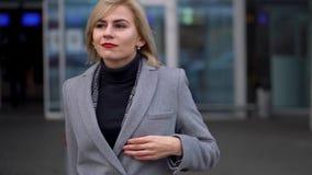 Το ξανθό κορίτσι σε ένα γκρίζο παλτό πηγαίνει στα πλαίσια ενός σύγχρονου κτηρίου γυαλιού απόθεμα βίντεο