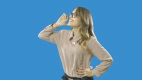 Το ξανθό κορίτσι σε μια μπλούζα σατέν φωνάζει ή καλεί κάποιο δυνατά και χαρωπά, συγκινήσεις, ενεργώντας σε ένα απομονωμένο μπλε απόθεμα βίντεο