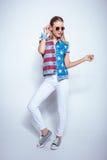 Το ξανθό κορίτσι στα γυαλιά ηλίου που φορούν τη φανέλλα τζιν με μας σημαιοστολίζει και που θέτουν στο στούντιο Στοκ Φωτογραφίες