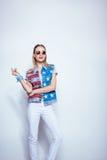 Το ξανθό κορίτσι στα γυαλιά ηλίου που φορούν τη φανέλλα τζιν με μας σημαιοστολίζει και που θέτουν στο στούντιο Στοκ εικόνες με δικαίωμα ελεύθερης χρήσης