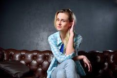 Το ξανθό κορίτσι στα τζιν κάθεται στον καναπέ δέρματος Στοκ Εικόνες