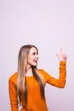 Το ξανθό κορίτσι στην πορτοκαλιά μπλούζα έδειξε επάνω στο λευκό στοκ εικόνα με δικαίωμα ελεύθερης χρήσης