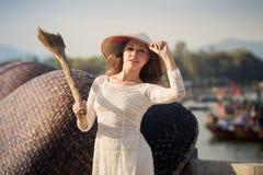 το ξανθό κορίτσι στο βιετναμέζικο φόρεμα κρατά τη σκούπα στο ανάχωμα Στοκ Εικόνες