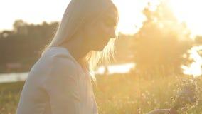 Το ξανθό κορίτσι στο ηλιοβασίλεμα συλλέγει τα λουλούδια φιλμ μικρού μήκους