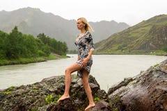 Το ξανθό κορίτσι στο κοντό φόρεμα στέκεται χωρίς παπούτσια στο W στοκ εικόνες