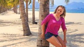 Το ξανθό κορίτσι στο ροζ κλίνει στα χαμόγελα τρίχας αφών φοινικών ενάντια στη θάλασσα απόθεμα βίντεο