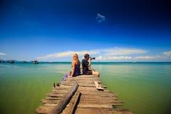 Το ξανθό κορίτσι τύπων κάθεται στην ξύλινη κυανή θάλασσα φωτογραφιών αποβαθρών στους τροπικούς κύκλους Στοκ Εικόνα