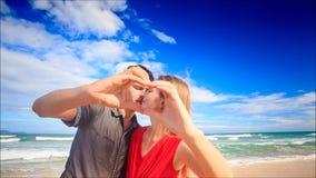 Το ξανθό κορίτσι τύπων κάνει το φιλί καρδιών δάχτυλων στην παραλία κυματωγών κυμάτων φιλμ μικρού μήκους