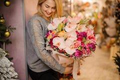 Το ξανθό κορίτσι χαμογελά και κρατά μια ανθοδέσμη των ρόδινων ορχιδεών και των ρόδινων τριαντάφυλλων Στοκ Εικόνα