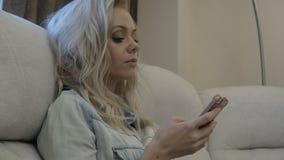 Το ξανθό κορίτσι χρησιμοποιεί το smartphone της απόθεμα βίντεο