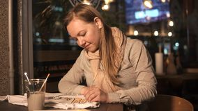 Το ξανθό κορίτσι χρωματίζει σε μια άσπρη μπλούζα από τη βούρτσα, καθμένος στον καφέ το βράδυ φιλμ μικρού μήκους