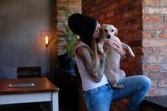 Το ξανθό κορίτσι Tattoed κρατά και φιλώντας το σκυλάκι της στο δωμάτιο με το εσωτερικό σοφιτών στοκ φωτογραφίες