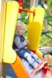 Το ξανθό μικρό παιδί κάθεται σε μια φωτογραφική διαφάνεια των παιδιών στην παιδική χαρά Στοκ εικόνα με δικαίωμα ελεύθερης χρήσης