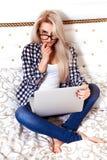 Το ξανθό νέο κορίτσι με τα μπλε μάτια κάθεται στο κρεβάτι με το lap-top Στοκ φωτογραφίες με δικαίωμα ελεύθερης χρήσης
