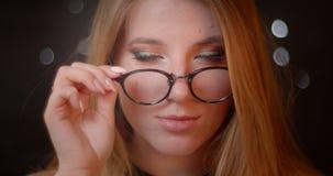 Το ξανθό πρότυπο με τη φωτεινή σύνθεση καθορίζει eye-glasses της φλερτάροντας με τη κάμερα στο υπόβαθρο bokeh απόθεμα βίντεο