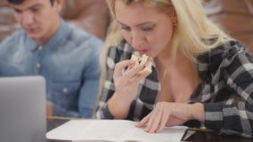Το ξανθό σημειωματάριο ανάγνωσης κοριτσιών που τρώει το σάντουιτς ενώ ο φίλος της που ερευνά τις πληροφορίες για το διαδίκτυο που απόθεμα βίντεο