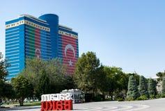 Το ξενοδοχείο του Αζερμπαϊτζάν Hilton βρίσκεται στην καρδιά κεντρικός Τουρκική σημαία του Αζερμπαϊτζάν και Πράσινη περιοχή πάρκων στοκ εικόνα